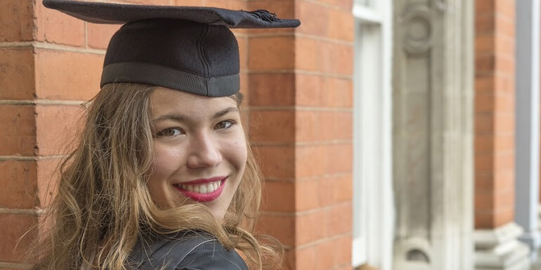 Smiling Female Graduate Posing in Black Cap and Gown